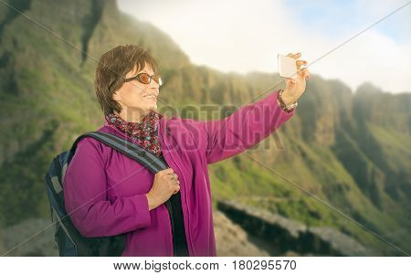 Hiking elderly smiling tourist photographing mountains with mobile phone. Standing aged woman in sunglasses wears red purple jacket colored muffler scarf and backpack. Travel concept. Mid shot on blurry highland background