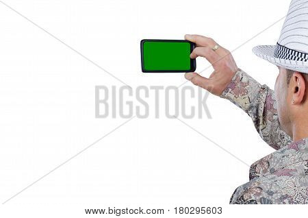 Back view of middle aged male tourist captures photo by mobile phone with chroma key screen. Man wears colored shirt and white hat. Travel concept. Close-up horizontal shot on white background