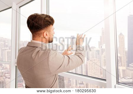 Futuristic technologies. Pleasant professional businessman standing near window and using transperant screen while workign in the office