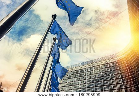 Waving EU flags in front of European Commission in Brussels at sunset