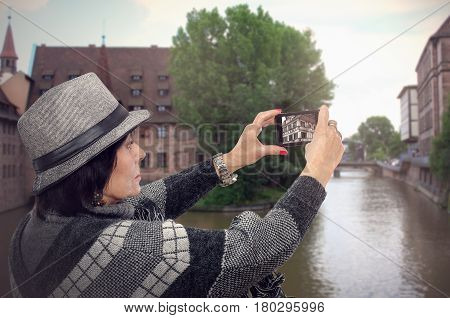 Elderly woman takes pictures of architecture of medieval European city on the river with mobile phone. Straight profile traveling woman. She wears poncho sweater and gray trilby hat. Travel concept. Mid shot on blurry background