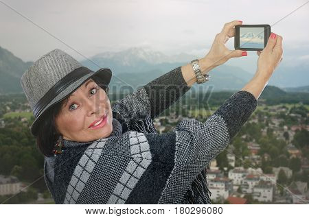 Traveling elderly woman takes pictures of snow-capped mountain top with mobile phone. Aged lady wearing poncho sweater and gray trilby hat. She turns head and looks at the camera. Travel concept. Mid shot on blurred highland city background