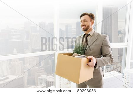 Join new team. Positive content handsome employee holding his belongings and standing in the office while getting ready to work