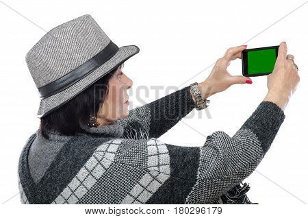 Elderly traveling woman takes pictures with mobile phone. She looks at chroma key screen. Straight profile of aged woman wearing poncho sweater and gray trilby hat. Travel concept. Mid shot on white background