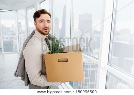 New period of life. Pleasant skillful employee holding box with his belongings and experincing first day at new workplace