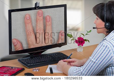 Telemedicine female dermatologist in headset looks at peeling off nails layers of female patient on monitor with attention. Virtual doctor sees falling off fingernails either by online video chat or snapshot. Horizontal mid-shot on blurry indoors backgrou poster