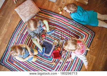 Top view of four little kids playing foods plates and tea time on the carpet on the floor in waldorf kindergarten