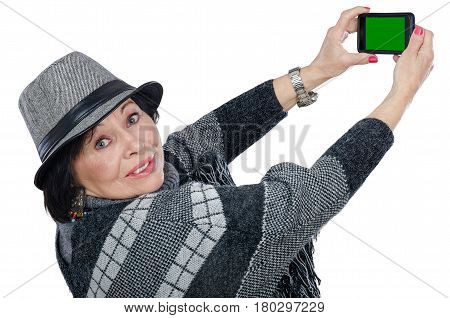 Traveling old lady holds mobile phone with chroma key screen. Aged woman wearing poncho sweater and gray trilby hat. She turns head and looks at the camera. Travel concept. Mid shot on white background