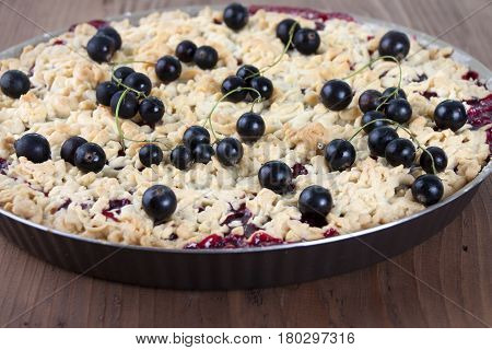 Sand cake with black currant in baking dish and currant berries