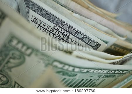 Macro detail of a one hundred dollar bank note in a row with many other bank notes