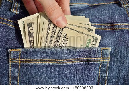 Male hand inserting or withdrawing heap of American money (US currency, USD) in the back pocket of blue jeans with yellow stitching as a symbol of black money earned without taxation
