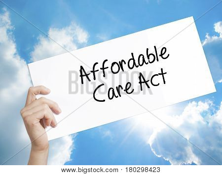 Man Hand Holding Paper With Text Affordable Care Act . Sign On White Paper. Isolated On Sky Backgrou