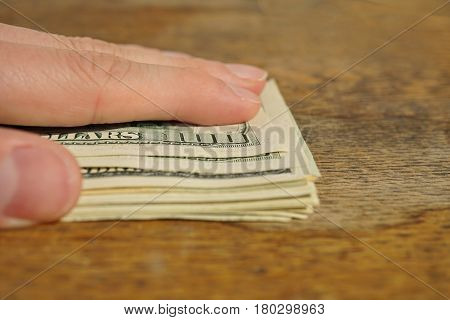 Male hand covering a heap of American money (US currency, USD) on the wooden background as a symbol of wealth