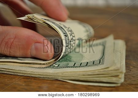 Male hand checking and counting a heap of American money (US currency, USD) on the wooden background as a symbol of wealth