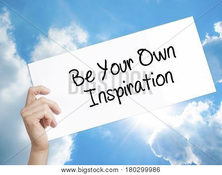 Man Hand Holding Paper With Text Be Your Own Inspiration . Sign On White Paper. Isolated On Sky Back