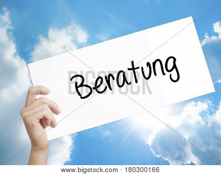 Man Hand Holding Paper With Text Beratung (advice In German) . Sign On White Paper. Isolated On Sky