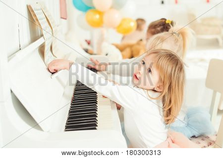Two cute little girls playing piano in the studio.