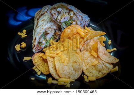 Chicken quesadilla wrap with chicken,corn,sweet pepper,salsa and chips.A quesadilla is a tortilla,usually a corn tortilla but also sometimes made with a wheat tortilla, which is filled with cheese and then grilled.