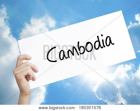 Man Hand Holding Paper With Text Cambodia  . Sign On White Paper. Isolated On Sky Background