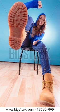 Unusual wide angle view of young woman teen girl long hair in hooded sweater showing sole boots on blue