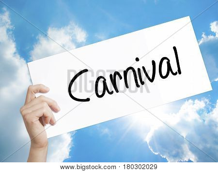Man Hand Holding Paper With Text Carnival . Sign On White Paper. Isolated On Sky Background