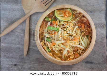 Green Papaya Salad (Som tum Thai) on wood table