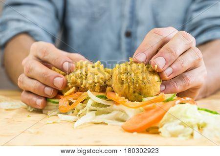 Making vegan flat bread sandwich with falafel. Male hands laying falafel balls fresh vegetables on lavash flat bread for making vegan kebab sandwich