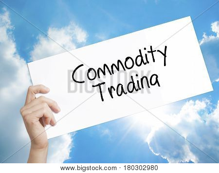 Man Hand Holding Paper With Text Commodity Trading . Sign On White Paper. Isolated On Sky Background