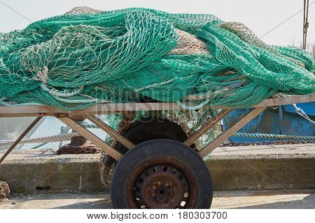 Industrial fishing nets on old kart at port