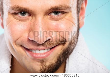 Closeup of happy man with half shaved face beard hair. Smiling handsome guy on blue. Skin care and hygiene.