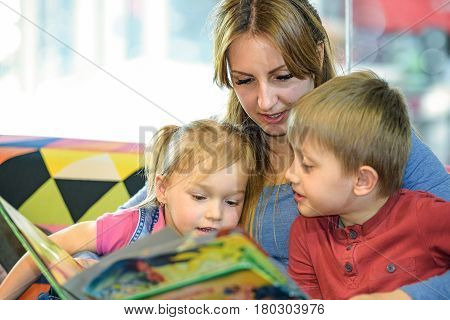 Portrait of pretty young women reading fairy tales with two children in the children's playroom
