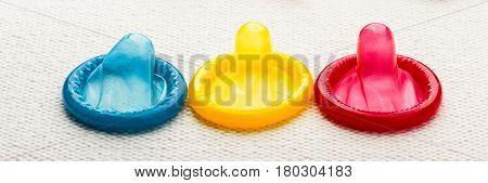 Healthcare medicine contraception and birth control. Closeup colorful condoms on white cloth.