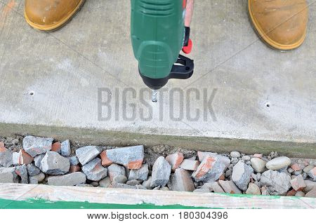 Drilling a hole in a concrete path with a electric drill