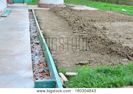 Construction works of a path beside a soil prepared for a lawn in a backyard