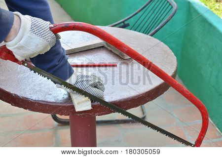 Worker's hands in a process of cutting wooden material with a saw