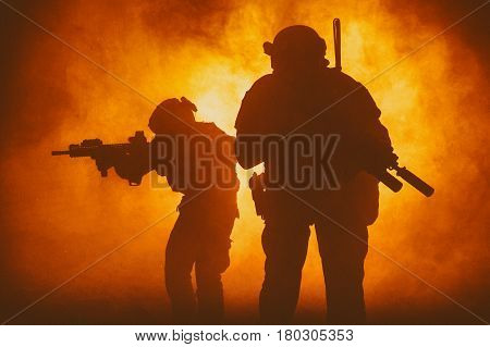 Black silhouettes of pair of soldiers in smoke moving through fire burning in battle operation, sacrificing their lives of our secutiry. Back light