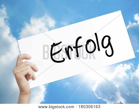 Man Hand Holding Paper With Text Erfolg Success (in German) . Sign On White Paper. Isolated On Sky B