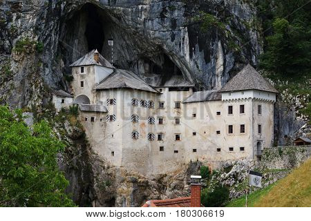 fifteenth-century Predjamski castle built into the cave in a rocks with a height of over one hundred meters. White with sloping roofs on a background of black rocks and green trees.