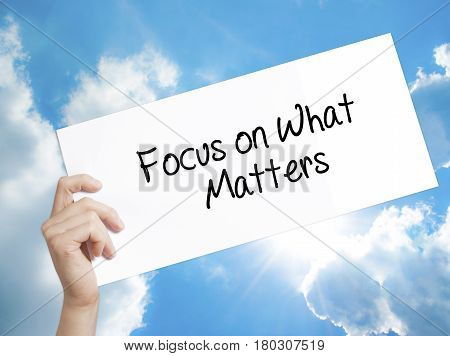 Man Hand Holding Paper With Text Focus On What Matters . Sign On White Paper. Isolated On Sky Backgr