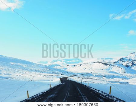 Curved Winter Asphalt Road With Mountain On The Side Of The Road Covered With Snow. Sunny Day And Cl