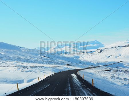Winter Road With Mountain On The Side Of The Road Covered With Snow. Sunny Day And Clear Blue Sky