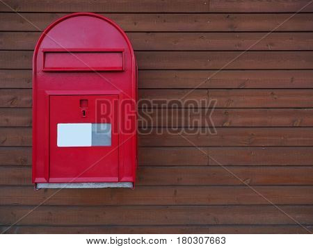 A new red mailbox with dark brown wooden background