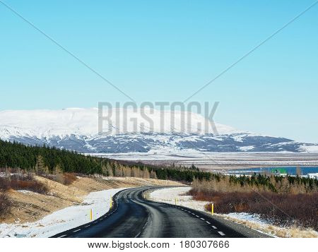 Curved Winter Asphalt Road With Trees And Mountain On The Side Of The Road Covered With Snow.