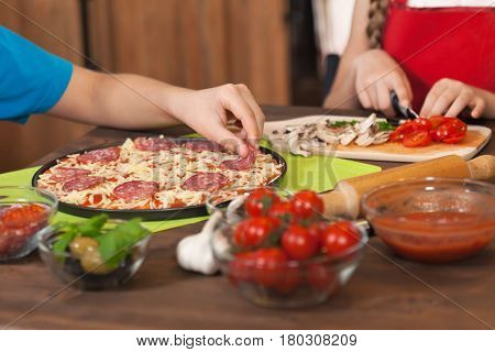 Kids making a pizza at home - preparing and placing the ingredients on the dough in the baking pan, closeup