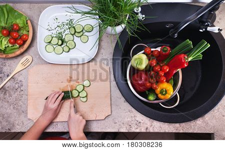 Child hands chopping vegetables on cutting board - making a fresh and healthy salad in the kitchen, top view of the sink area