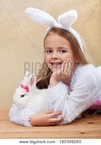 Little girl in bunny costume holdng her white rabbit lying on the floor