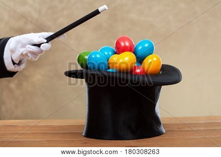 Magician hand with magic wand bringing the easter eggs in a hard hat - on golden background