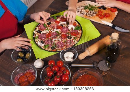 Kids making a pizza - preparing and placing the ingredients on the dough in the baking pan - the finishing touches