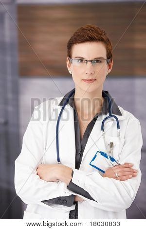 Young confident medical doctor standing in office in uniform with arms folded, smiling at camera?