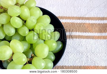 Lot of ripe green grape berries on bunche in black round bowl on striped fabric background top view close up